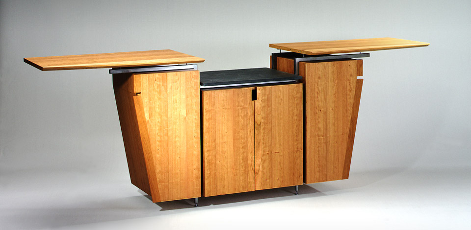 <p>Dining Cabinet</p><p>1995</p><p>Designed as a multi-purpose Dining room cabinet for a residence in West Vancouver. The top slides open allow for more surface area to place hot foods on the granite top.</p><p>Cherry veneer plywood, with aluminum roll-top fronts,and wheels.</p><p>Height 38'' Depth 23'' Length 76'' Extended 108''</p>